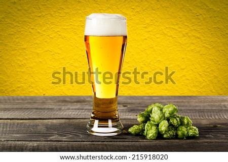 Glass beer with hops on wood background with copyspace