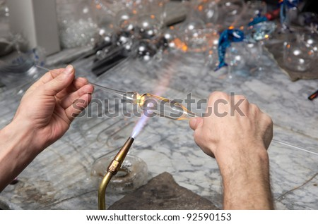 Glass blower forming a piece of decorative glass