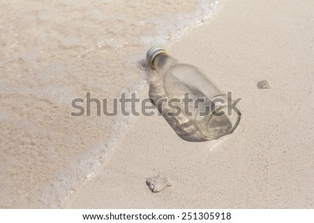 Glass bottle and small broken corals washed up as rubbish on a beach, garbage on beach, concept of beach environment. - stock photo