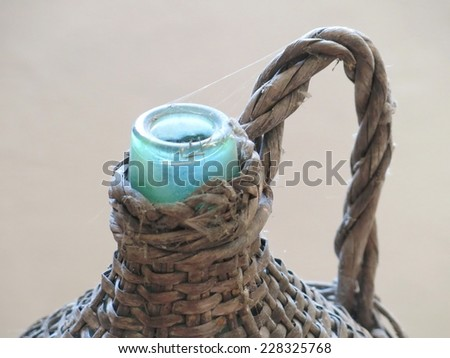glass bottle antique Wicker-clad to hold wine and oil - stock photo