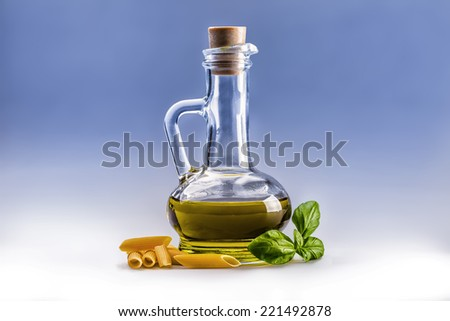 Glass bottle carafe with olive oil penne pasta and basil leaves on white and blue background.