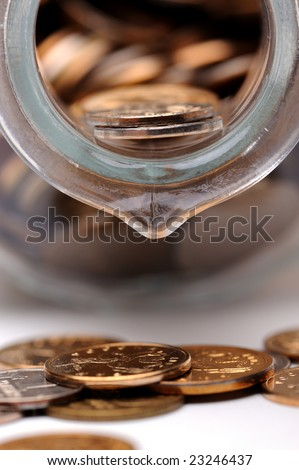 Glass bottle full of coins on a white background