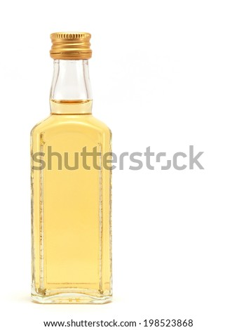 glass bottle full of the liquid of yellow color on a white background - stock photo