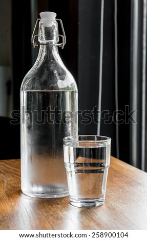 Glass bottle of cold fresh water with drinking glass. - stock photo