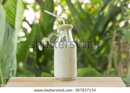 Glass bottle of Fresh Milk on the table - stock photo