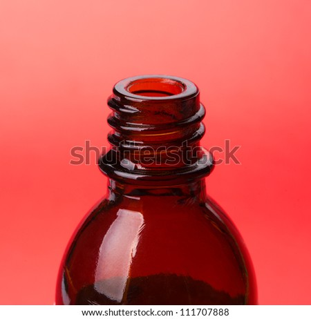 Glass bottle of medical drops on red background
