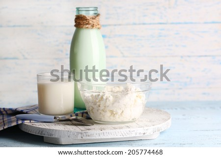 Glass bottle of milk and cottage cheese on wooden background - stock photo