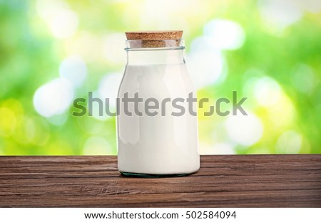 Glass bottle of milk on wooden table against blurred nature background. Dairy concept.