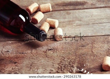 Glass bottle of wine with corks on wooden table background - stock photo