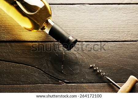 Glass bottle of wine with corkscrew on wooden table background - stock photo