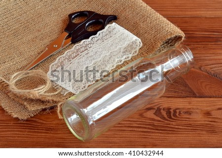 Glass bottle, scissors, burlap, cord, lace. Set for handmade vase. Rustic style. Brown wooden background.