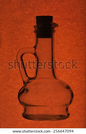 glass bottle with cork on red background - stock photo