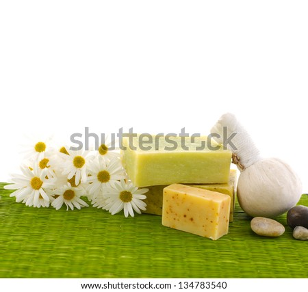 Glass Bottle with daisy flowers, stone, massage ball on green mat