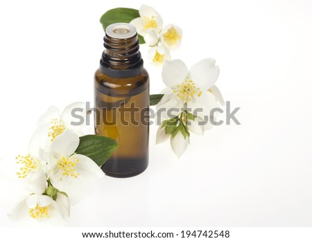 Glass bottle with essential oil and flowers on a white background.