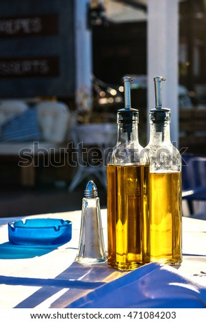Glass bottle with olive oil on a translucent gold setting sun