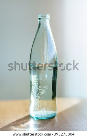 Glass bottle with pure water with sunlight. Film effect. - stock photo
