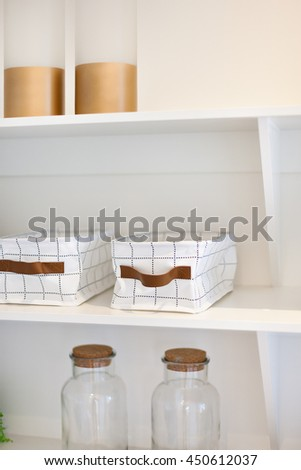 Glass bottles and baskets made into clothing with a line art in the wooden shelf including thick bottles