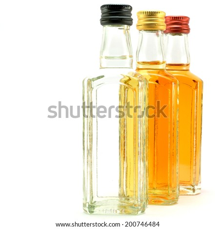 glass bottles filled with liquids of different colors on a white background