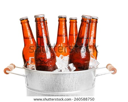 Glass bottles of beer in metal bucket isolated on white - stock photo