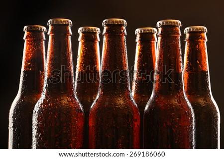Glass bottles of beer on dark background - stock photo