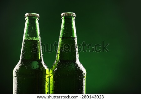 Glass bottles of beer on dark green background
