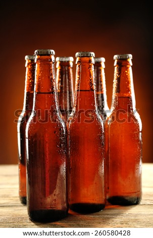 Glass bottles of beer on wooden table on dark background - stock photo