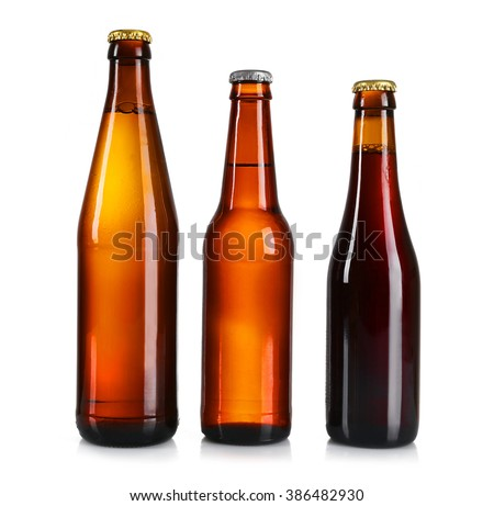 Glass bottles of different beer on light grey background - stock photo