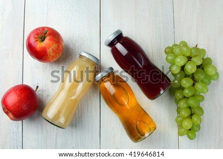 glass bottles of juice and an Apple with grapes on a white wooden background - stock photo