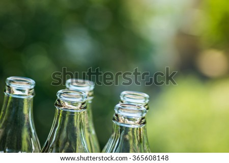 Glass bottles over the green sunny background