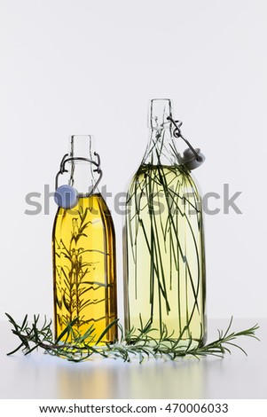Glass bottles with oil and vinegar and pickled herbs