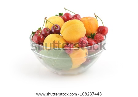 Glass bowl full of fresh delicious berries on white background