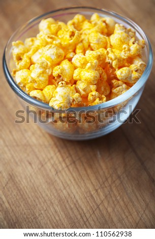Glass bowl of cheese popcorn on old wooden cutting board - stock photo