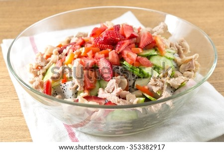 Glass Bowl of Delicious Chicken Salad with Strawberries, Dragon Fruits, Cucumbers and Tomatoes.
