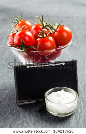 Glass bowl of fresh ripe red cherry tomatoes and savory creamy vinaigrette sauce on a slate background with a blank vintage school slate with copyspace for your text - stock photo