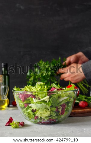 Glass bowl of fresh salad on a dark background. In background mode man holding bunch of parsley - stock photo
