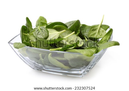 Glass bowl of fresh spinach on white background