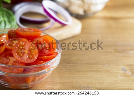 Glass bowl of sliced cherry tomatoes with other ingredients including red onion slices, all to the left side of image with wooden table top to right providing copy space.  Horizontal image. - stock photo