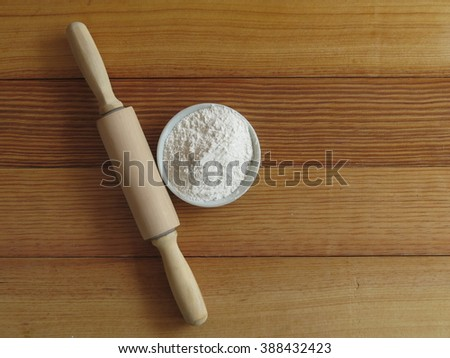 glass bowl of soft wheat flour, with wooden rolling pin on wood background
