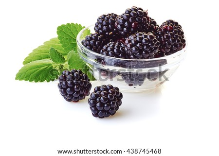Glass bowl with blackberries and mint leaves on white - stock photo