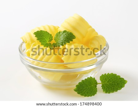 glass bowl with butter curls, decorated with herbs