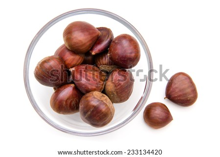Glass bowl with chestnuts on white background top view