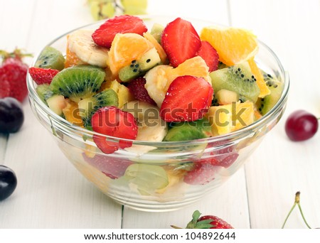 glass bowl with  fresh fruits salad and berries on white wooden table