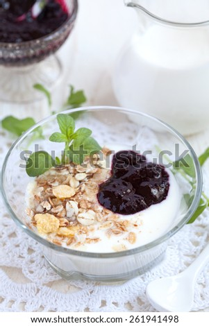 Glass bowl with homemade yogurt and granola (sunflower seeds, corn, oat and barley flakes and nuts) and blackcurrant jam, selective focus - stock photo