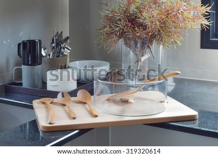 Glass bowl with wooden utensil on wooden tray in the kitchen - stock photo