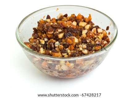 Glass bowl Xmas Cake Mix of nuts and soft fruits soaking up added rum, brandy and sherry. - stock photo