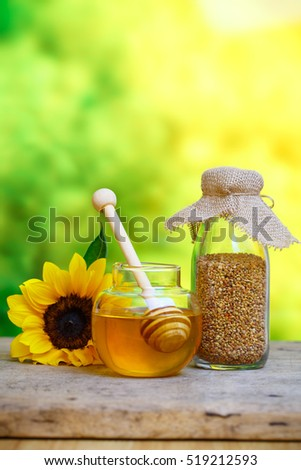 Glass bowls with honey another with pollen. Honey dipper, sunflower on the wooden background
