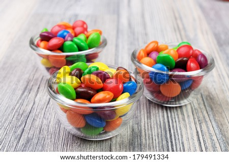 Glass bowls with multicolor candies - stock photo