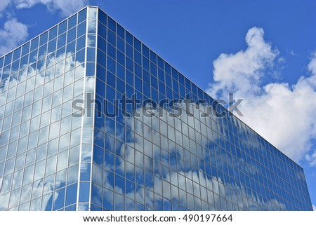 glass building in Grand Rapids Michigan with white cloud and blue sky reflection