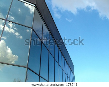 Glass building with clouds reflecting in windows