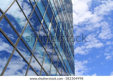 Glass business building with blue sky in background. Blue glass building where the business is done. Offices in glass business building. Open space and modern architecture for people and companies.